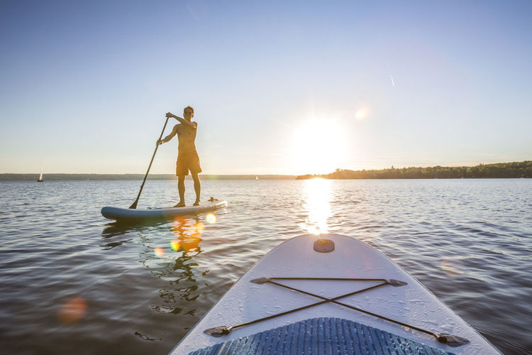 Full length of man on paddle board in sea during sunset