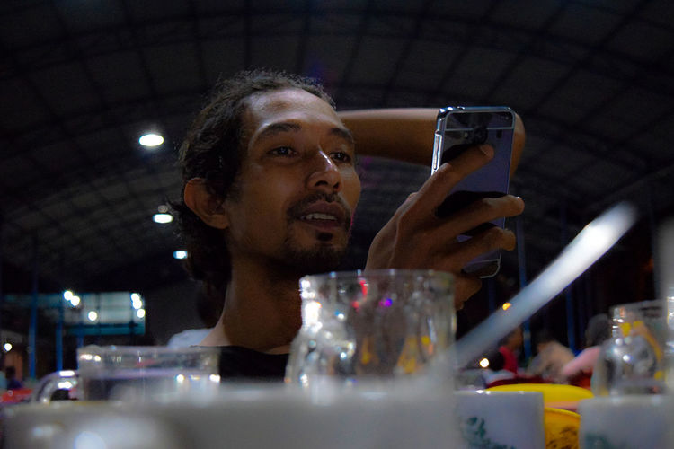 Low angle view of young man using mobile phone at restaurant