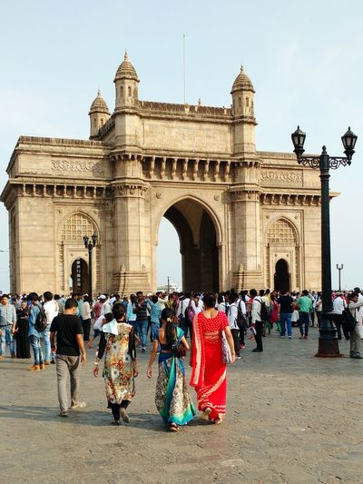 Crowd walking towards gateway to india against sky