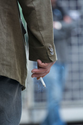 Midsection of man smoking cigarette