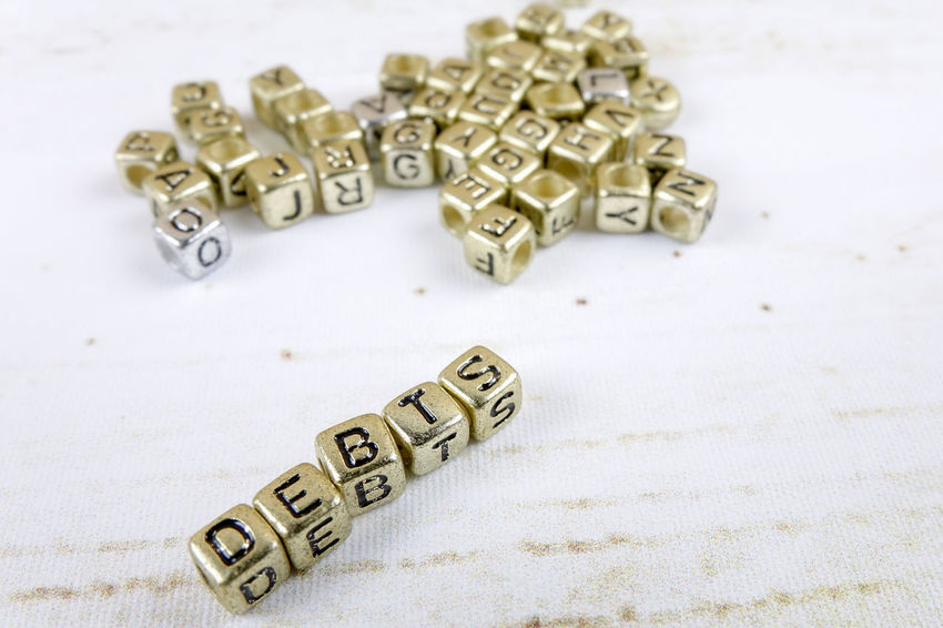 DEBT CONCEPT WITH GOLD DICE ON A WOODEN TABLE Capital Letter Close-up Communication Credit Card Debt Crisis Focus On Foreground High Angle View Indoors  Large Group Of Objects Metal No People Number Silver Colored Still Life Studio Shot Table Text Toy Wealth Western Script White Background White Color Wood - Material