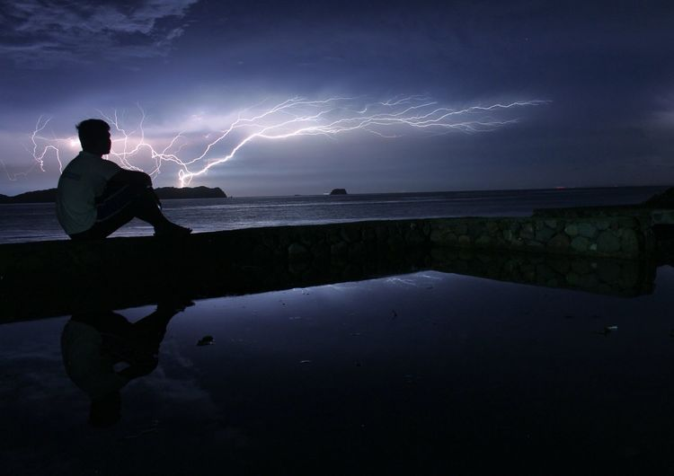 Man sitting by sea against sky at night