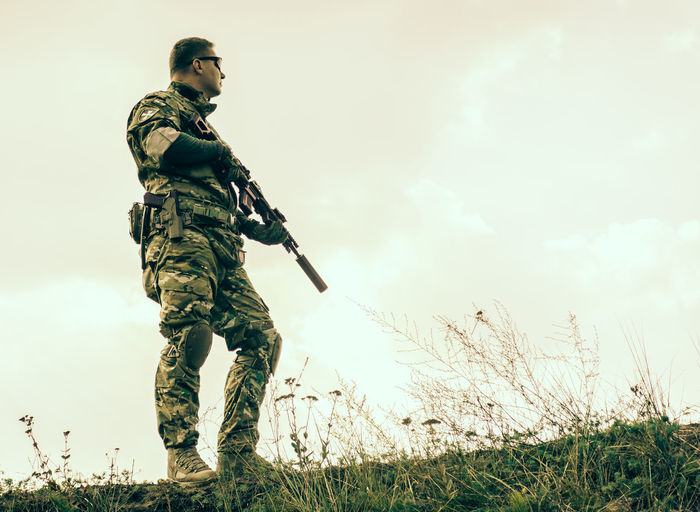 Full length of soldier with rifle standing on field against clear sky
