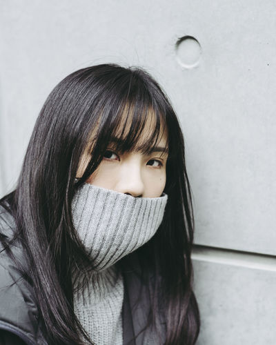 Close-Up Portrait Of Young Woman Covering Mouth With Turtleneck Against Wall