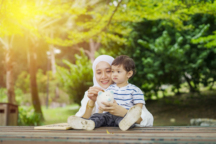 Young woman with her cute son learn how to put coins into piggy bank. Future planning concept. Child Childhood Togetherness Family Males  Men Bonding Son Innocence Boys Two People Sitting Offspring Casual Clothing Emotion Smiling Day Full Length Happiness Outdoors Positive Emotion