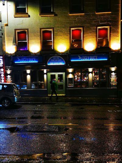 Illuminated street lights in city during rainy season