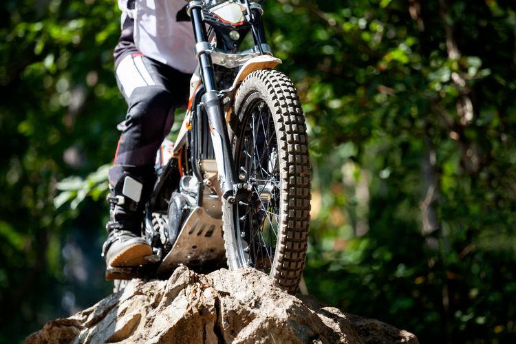 Low section of man riding motor bike on rock