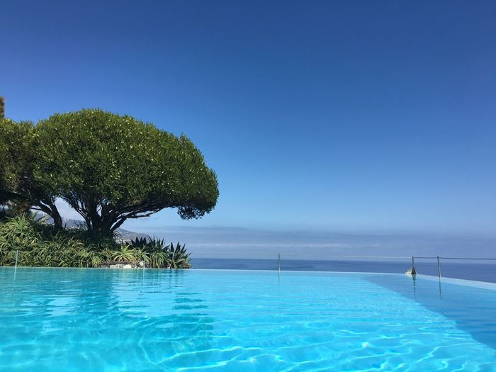 Swimming pool by sea against clear blue sky