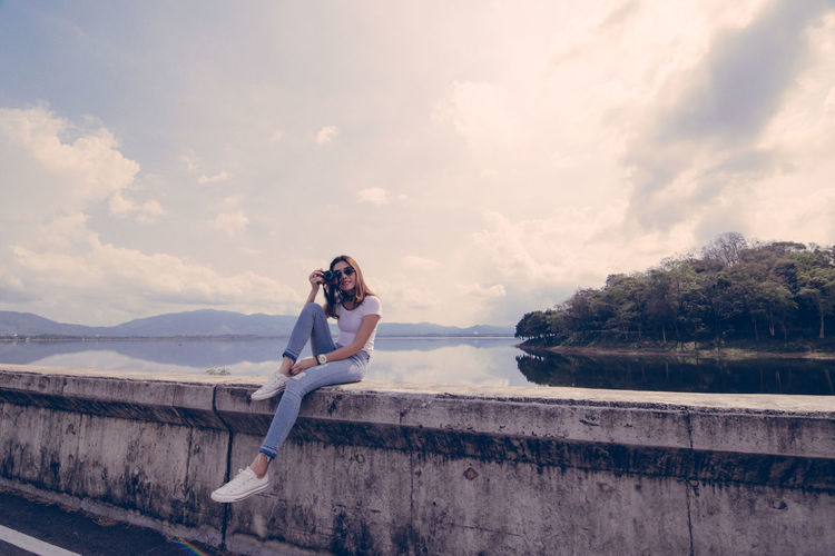 Portrait of woman photographing while sitting against lake and sky