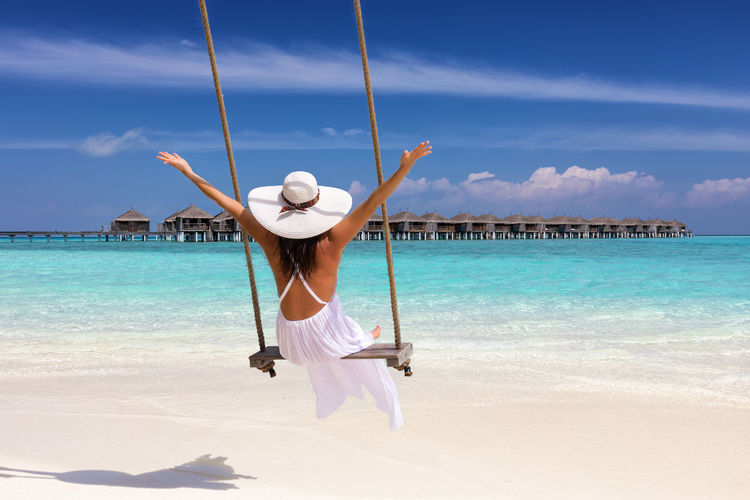 Happy traveler woman in white summer dress sits on a swing and enjoys her tropical vacation time Sky Sea Water One Person Leisure Activity Beach Beauty In Nature Lifestyles Trip Holiday Day Sunlight Vacations Turquoise Colored Arms Raised Outdoors Full Length Travel Concept Swing Tropical Climate Maldives Dress White Traveler