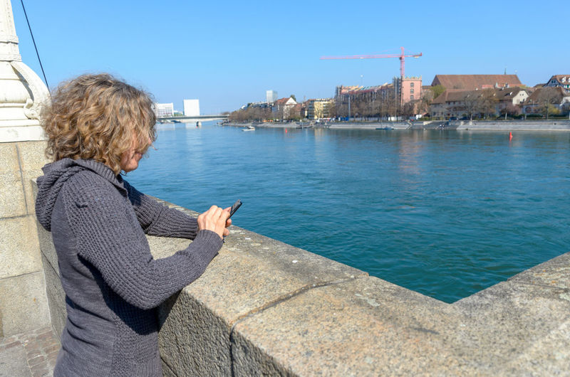 Rear view of woman using mobile phone over river against sky