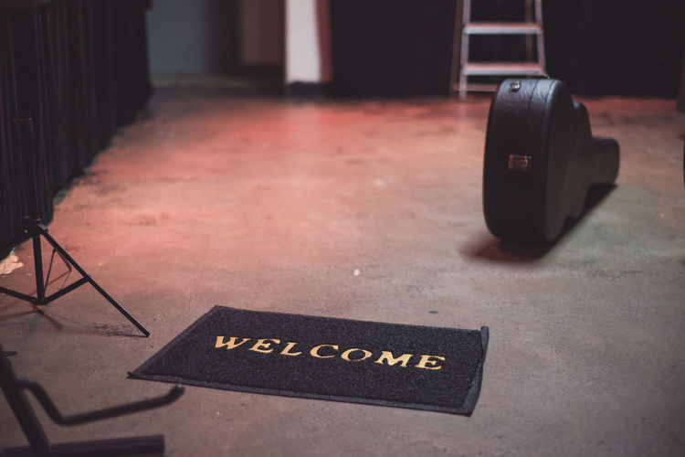High angle view of welcome sign on doormat by guitar case on floor