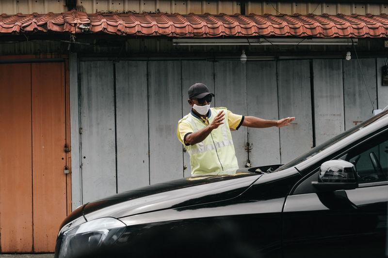 Man wearing mask stopping car in city