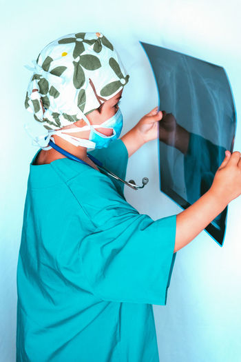 Side view of boy wearing mask holding medical x-ray