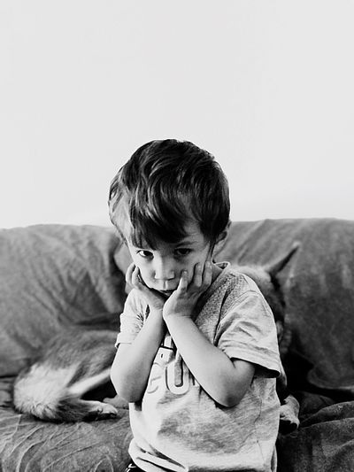 Portrait of boy with hand on chin sitting at home