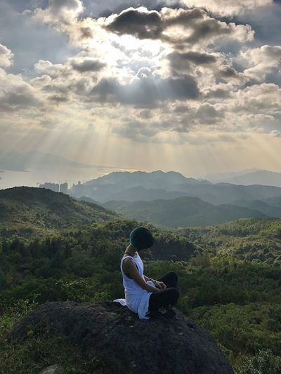 Woman Sitting On Landscape Against Mountains