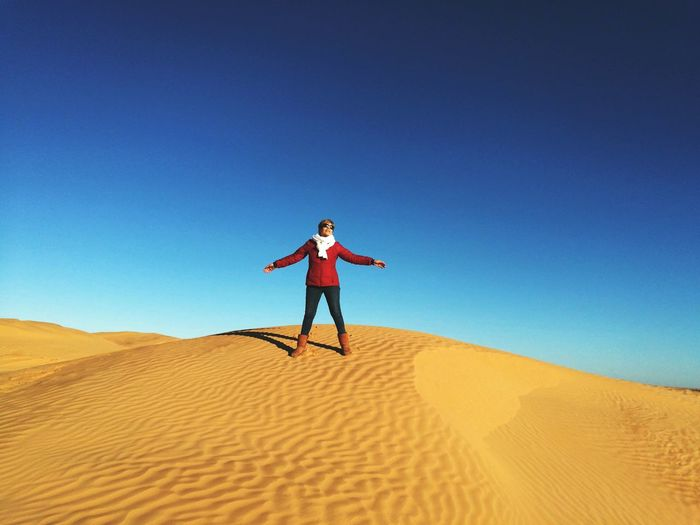 Woman with arms outstretched standing on sand dune in desert against clear blue sky