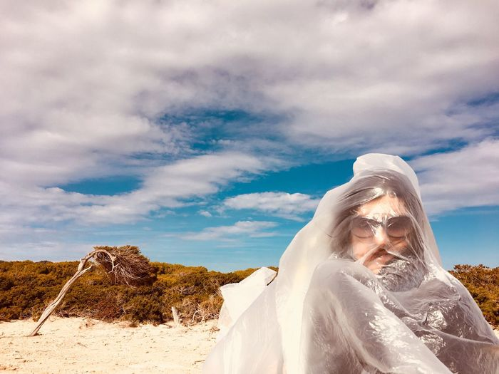 Portrait of woman face covered in plastic against cloudy sky