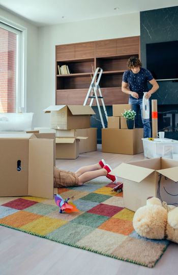 Little boy playing inside a moving box while his father unpacks in the living room Family Fun Happiness Happy Lying Moving Unpacking Apartment Boxes Boy Cardboard Home Interior House Indoors  Inside Lifestyles Living Room New Home Packing Placing Playing Real People Relocating Unrecognizable Person Vertical