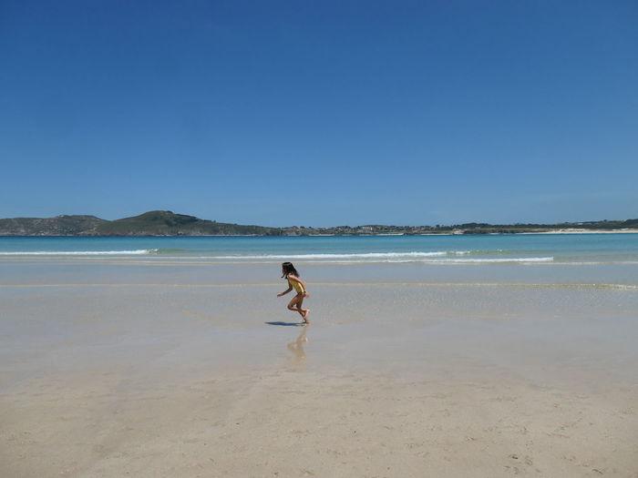 Man walking on beach against clear sky