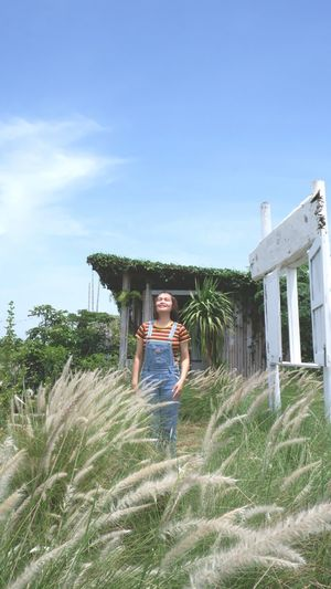 Portrait of woman standing by plants against sky