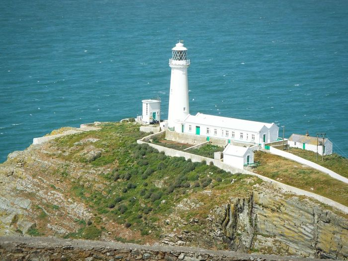 High angle view of whitewashed lighthouse by sea
