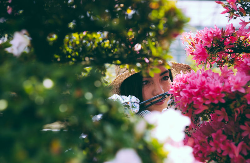 Close-up of woman by pink flowering plants outdoors