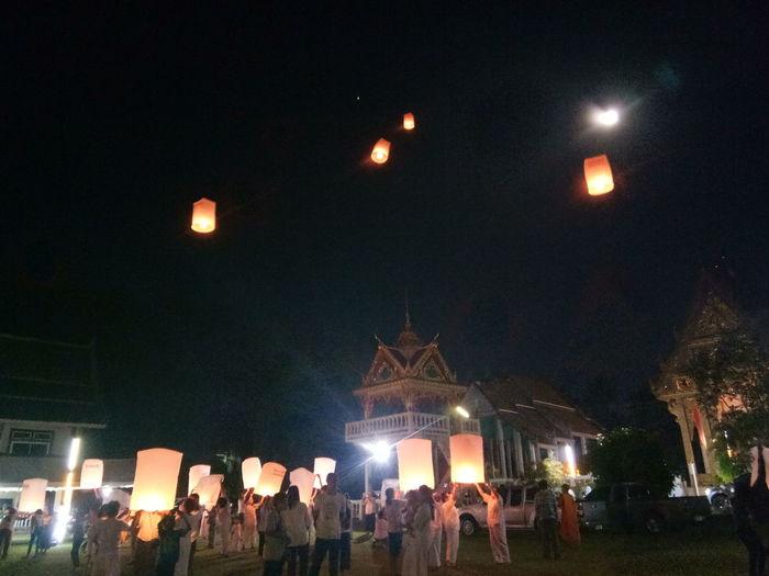 Group of people on illuminated street at night