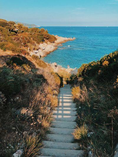 Steps leading towards sea against sky