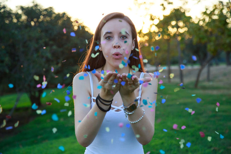 Portrait Of Young Woman Blowing Confetti While Standing At Park