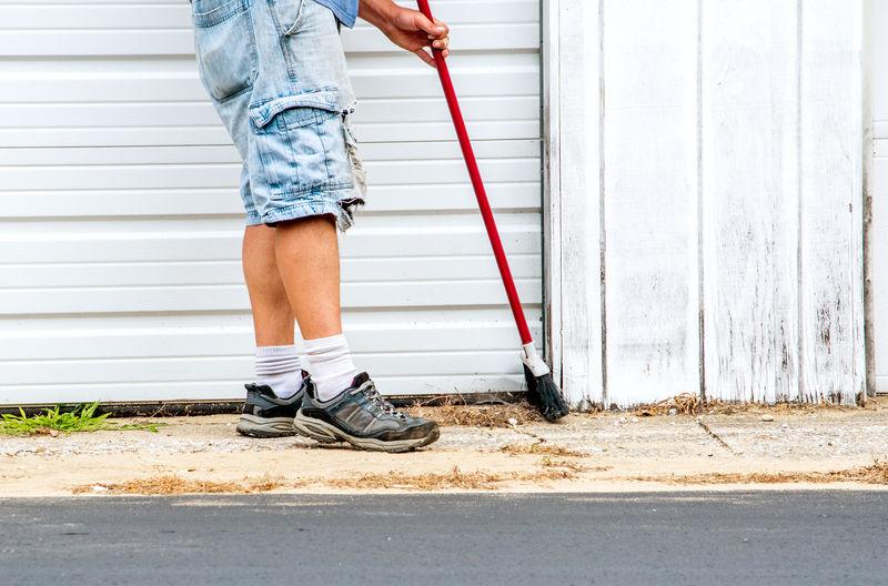 A worker sweeps up debris around a garage area