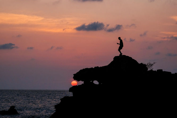 Silhouette rock in sea against sky during sunset