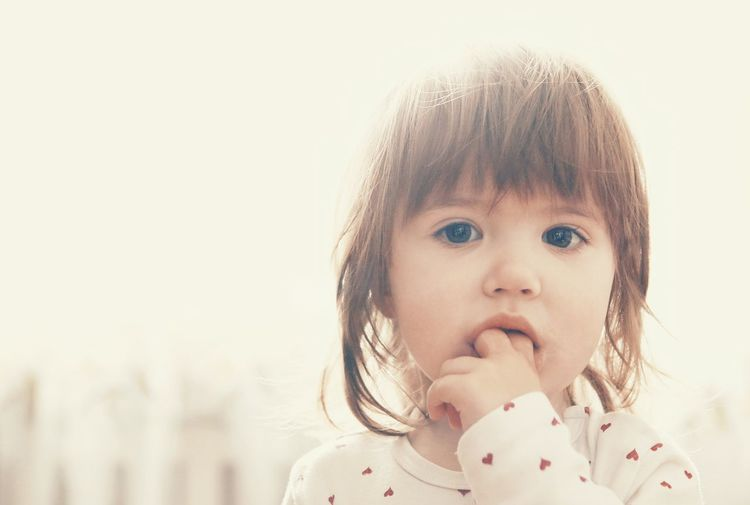 Portrait of cute girl with fingers in her mouth looking at camera