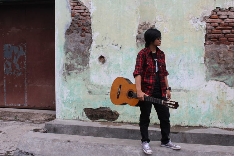 Full length of young woman holding guitar while standing by wall