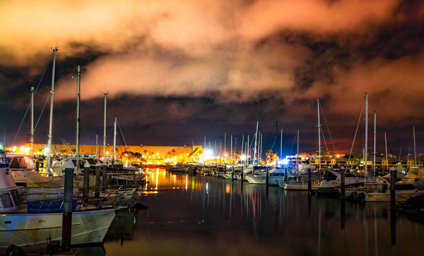Boats moored at harbor against sky during night