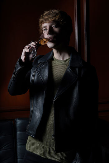 One Person Indoors  Front View Waist Up Holding Young Adult Three Quarter Length Clothing Looking At Camera Adult Standing Real People Lifestyles Leisure Activity Sitting Food And Drink Portrait Guy Drinking Glass Wine Biker Jacket Style Fashion Fashion Model Fashion Photography Shadows