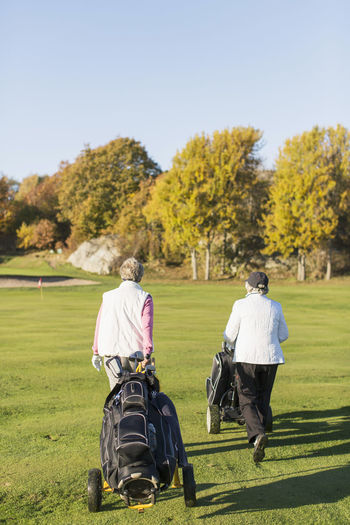 Rear view of people on golf course