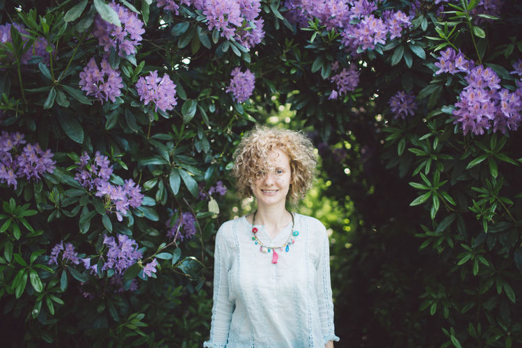 Portrait of smiling woman standing by purple flowering plants