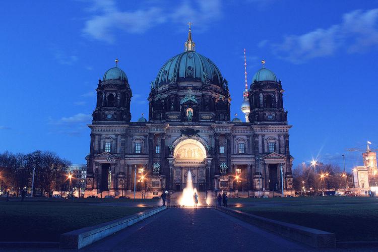 Illuminated church against blue sky