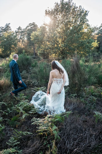 Newlywed couple walking in forest