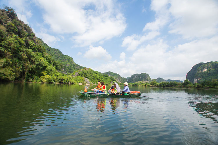 tourist sitting on boat at Trang An, Ninh Binh, Vietnam. Water Nautical Vessel Transportation Beauty In Nature Sky Mode Of Transportation Group Of People Day Waterfront Scenics - Nature Real People Nature Cloud - Sky Men Mountain Leisure Activity Tree Tranquility River Outdoors