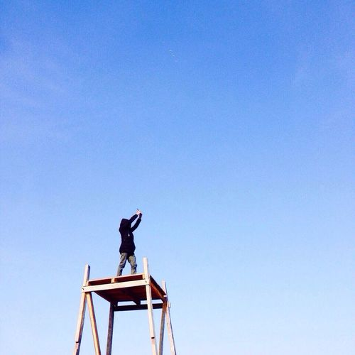 Low angle view of person on lookout tower taking picture with camera