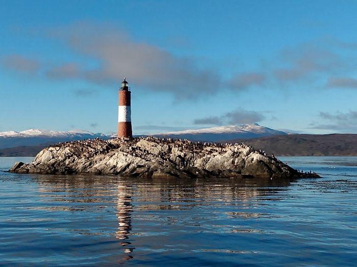 Lighthouse on building by sea against sky