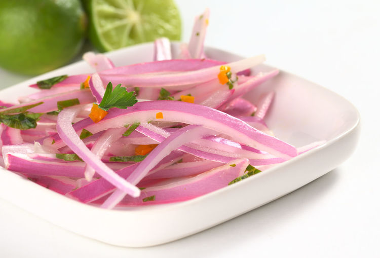 Peruvian Salsa Criolla made of red onion slices, hot pepper called aji, fresh parsley and limes (Very Shallow Depth of Field, Focus on the onion slice in the middle) Aji Criolla Sauce Homemade Hot Pepper Peru Peruvian Food Red Side Dish Vegetarian Food Accompaniment Appetizer Criolla Criollo Food Fresh Lime Onion Parsley Pepper Peruvian Red Onion Salsa Salsa Criolla Vegan Vegetable