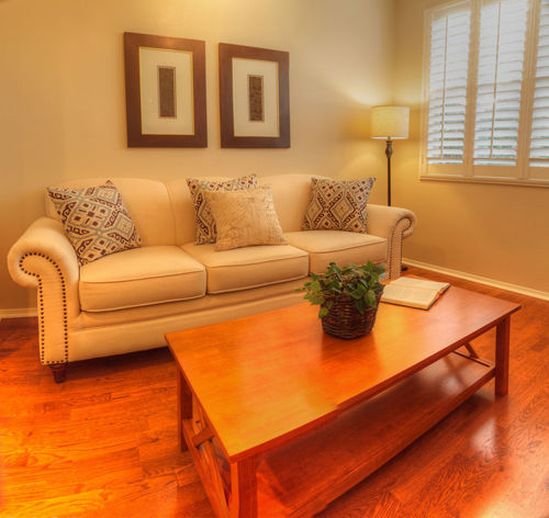Small living room with a sofa, coffee table, lamp, recessed lighting, wood floors and feng shui decor. Bay Window Clean House Coffee Table Day Domestic Room Home Interior Home Showcase Interior Horizontal Indoors  Living Room No People Plantation Shutters Shutters Wood Floor Zen