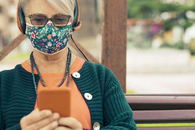 Senior woman wearing mask using smart phone outdoors