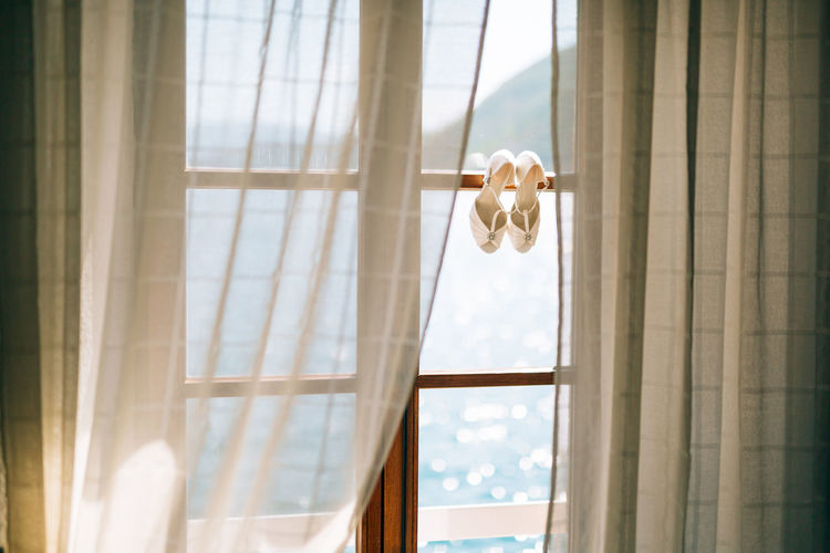 View of sandals hanging on window