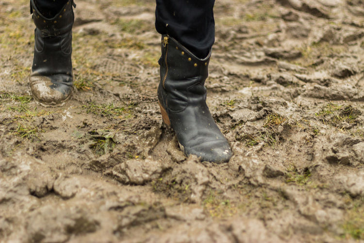 Low section of person walking on muddy field