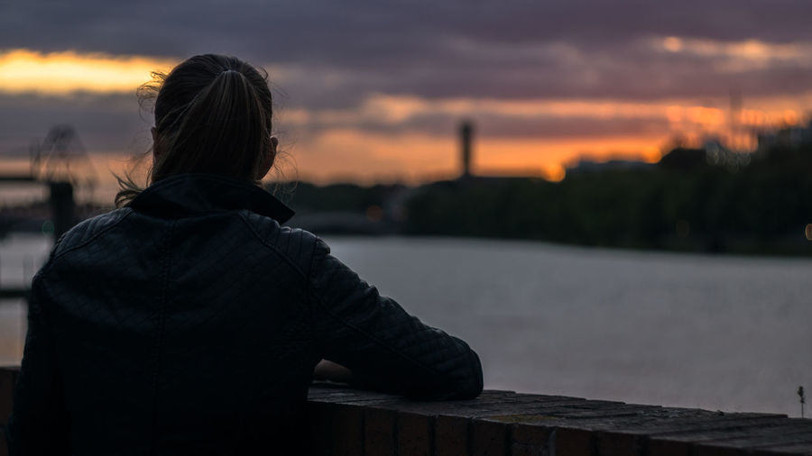 Rear View Of Woman Leaning In Railing By River Against Cloudy Sky During Sunset
