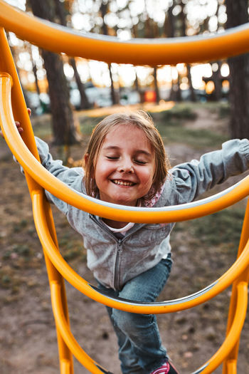 Playful happy girl preschooler playing on a playground climbing on monkey bars